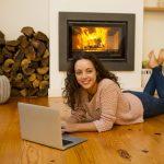 Femme sur ordinateur devant un feu de bois